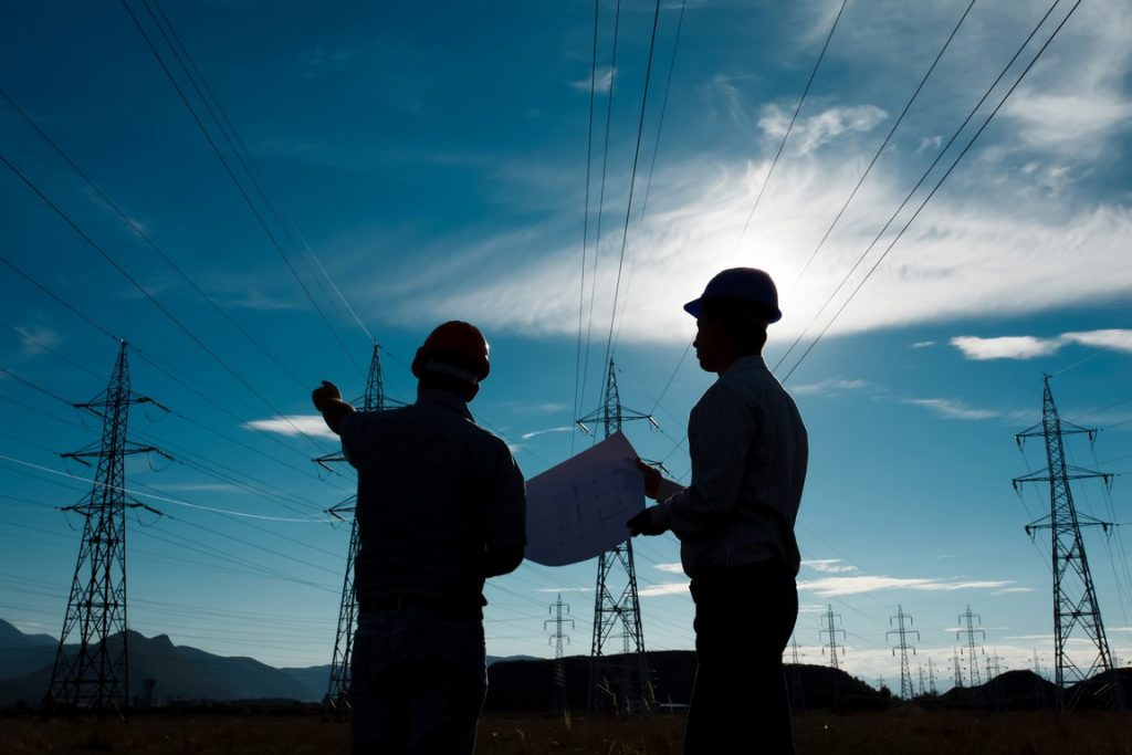 silhouette of two engineers standing at electricity station, discussing plan